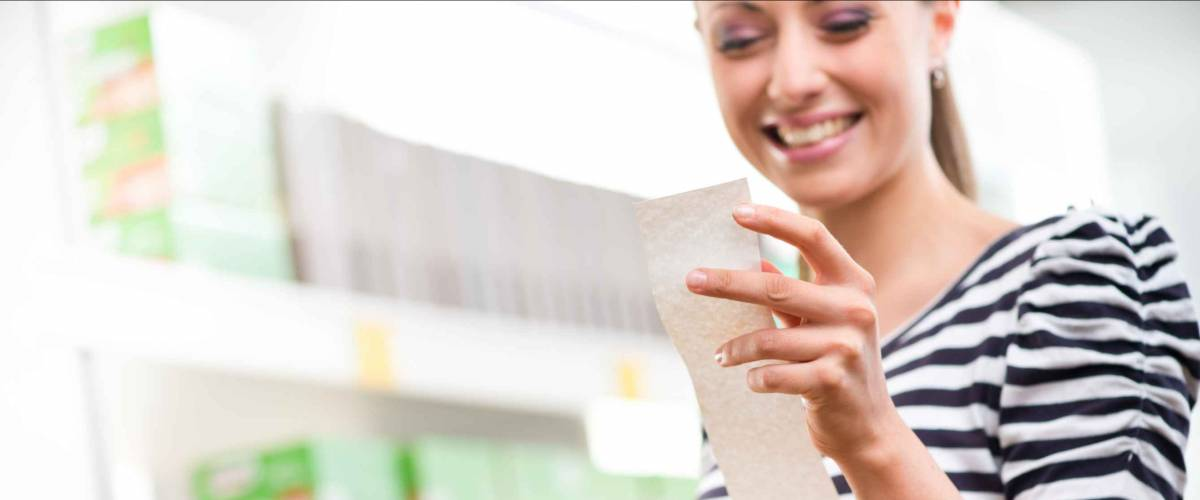 Smiling young woman holding a long grocery receipt at supermarket.