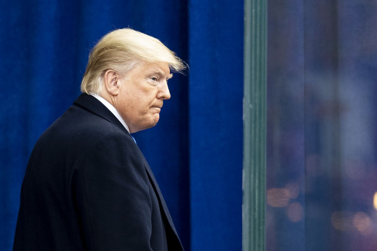 President Donald Trump, in a navy suit, looks past a bulletproof glass divider after a speech in New York.