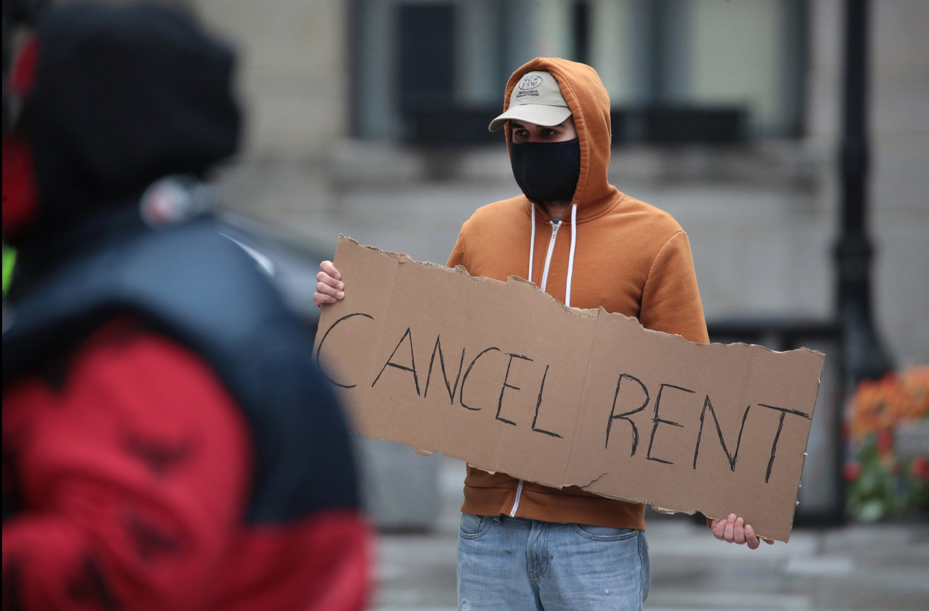 A Chicago protester holds a sign calling for rent to be canceled