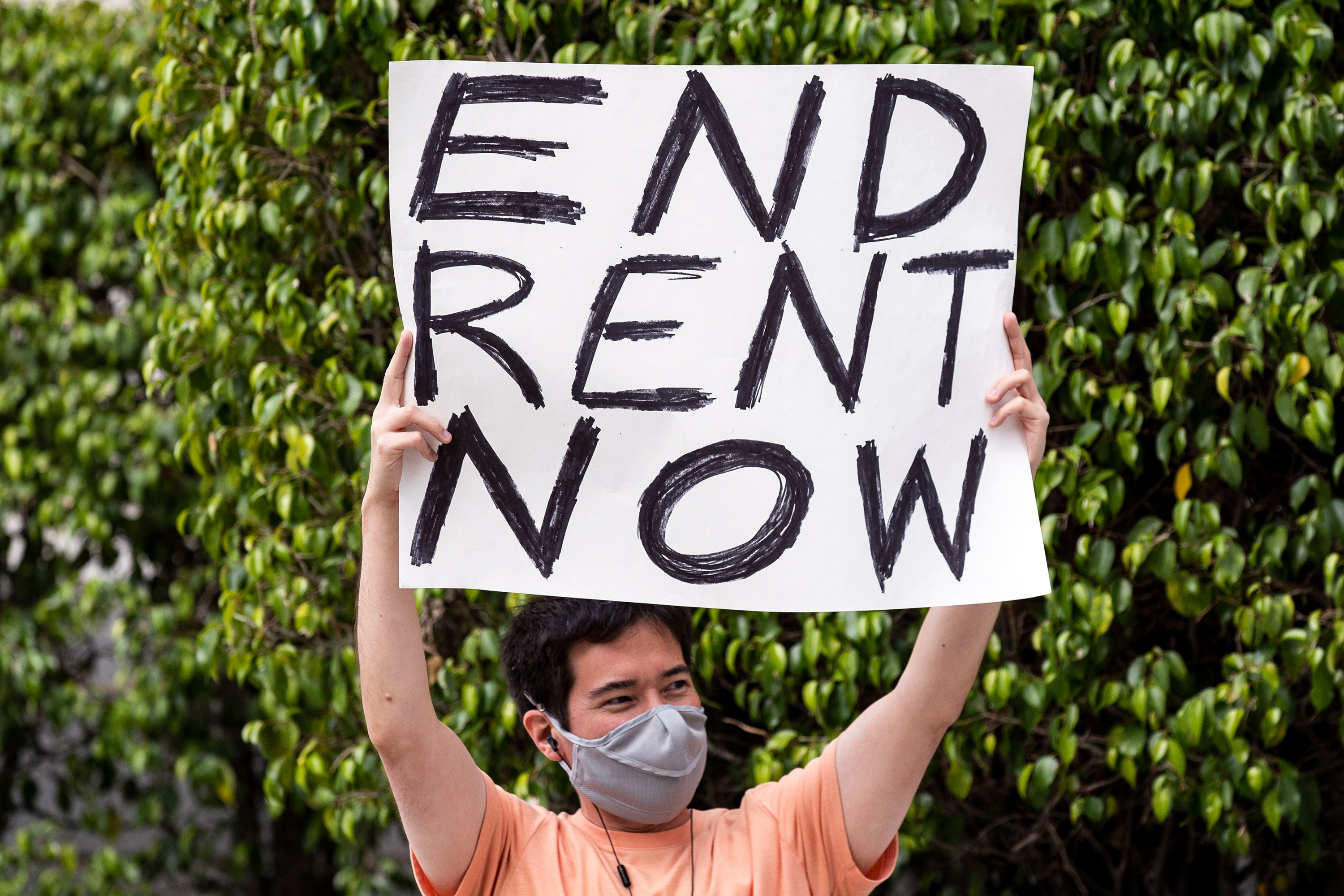 A man in Los Angeles holds a sign that reads: 'END RENT NOW'
