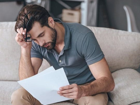 A tired-looking man resting his forehead on his hand while reading paperwork.