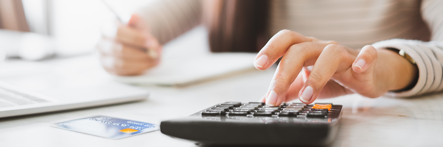 A woman budgeting her finances on a calculator.