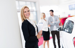 a smiling blond woman car salesman helping out a couple shop for a vehicle inside a car dealership