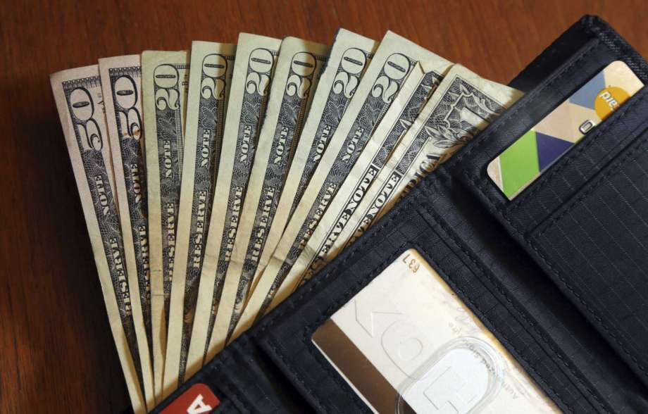 FILE - In this June 15, 2018, file photo, cash is fanned out from a wallet in North Andover, Mass.  High-interest payday and online lenders have long been among the few options for Americans with bad credit and lower incomes. Guidance issued in the spring by federal regulators cut a previously suggested rate cap on loans and that could mean banks start lending small-dollar, high-interest loans. (AP Photo/Elise Amendola, File) Photo: Elise Amendola / Copyright 2018 The Associated Press. All rights reserved.