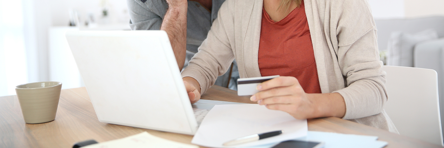A couple looks at a computer while holding a credit card.