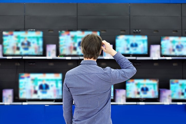 A man standing in front of a wall of TVs in an electronics store.