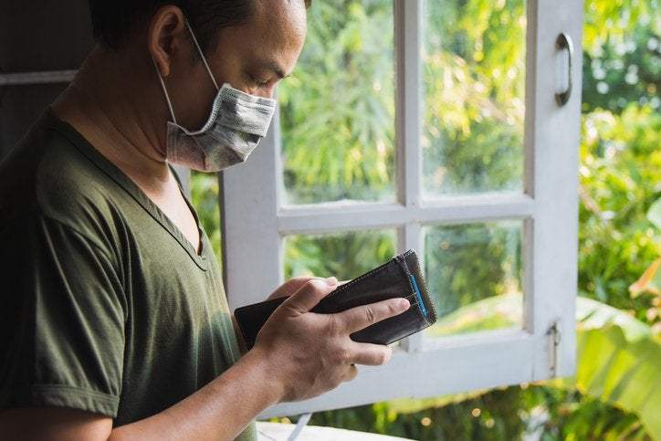 A man in a medical mask checks his wallet.