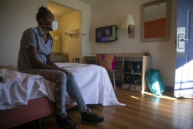 Jamie Burson sits on the bed of her motel room in Farfield on August 4, 2020. Burson, who has been living between her car and motels since being evicted in April, said she feels unsafe at the motel and planned to move again later later that day. - ANNE WERNIKOFF FOR CALMATTERS
