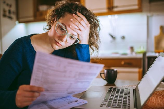 A woman reads over her credit card statements in this stock photo. A credit score above 680 is considered...
