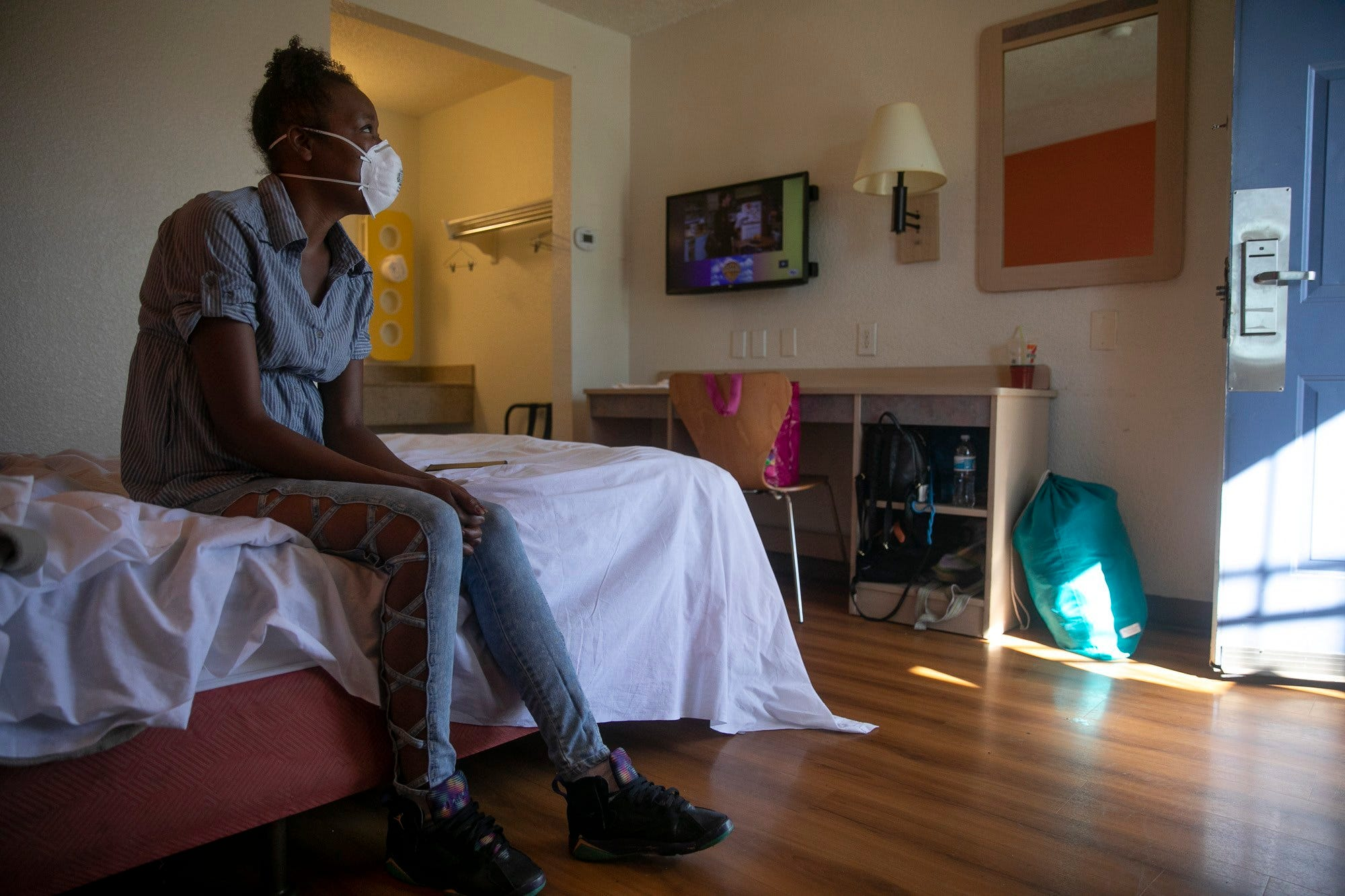 Jamie Burson sits on the bed of her motel room in Farfield on August 4, 2020. Burson, who has been living between her car and motels since being evicted in April, says she feels unsafe at the motel and plans to move again later later today.