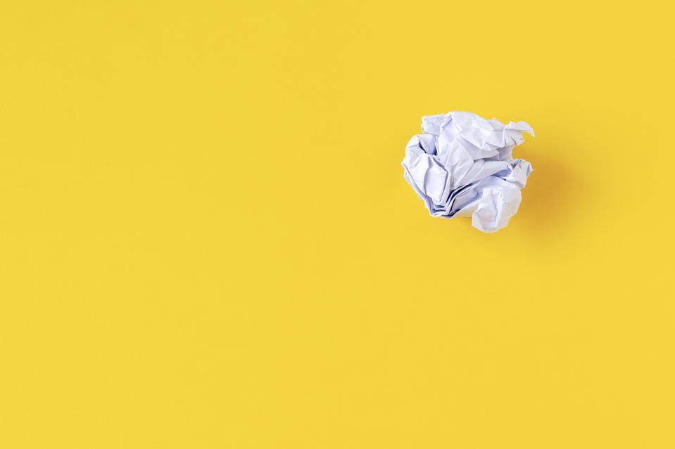 Crumpled Paper Ball on Yellow Background