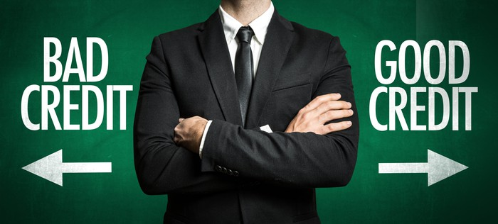 Man in suit standing with arms crossed with graphics reading BAD CREDIT and GOOD CREDIT on either side of him.