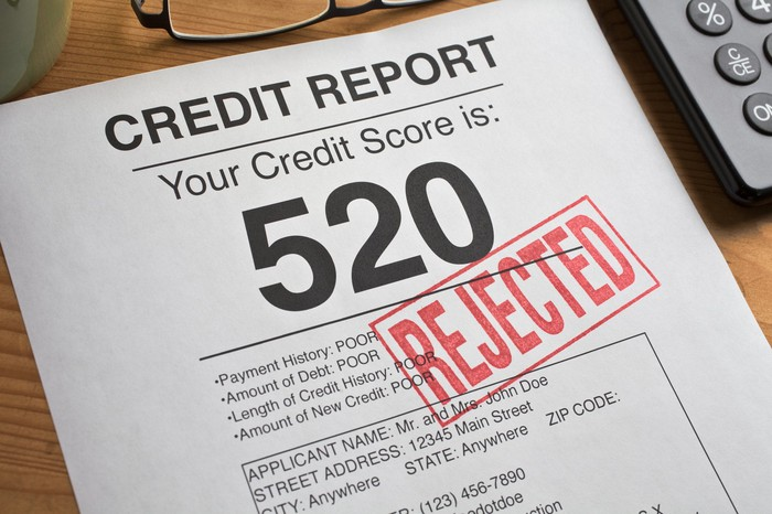 Sheet of paper showing a bad credit score of 520 with a red stamp over it that reads REJECTED.