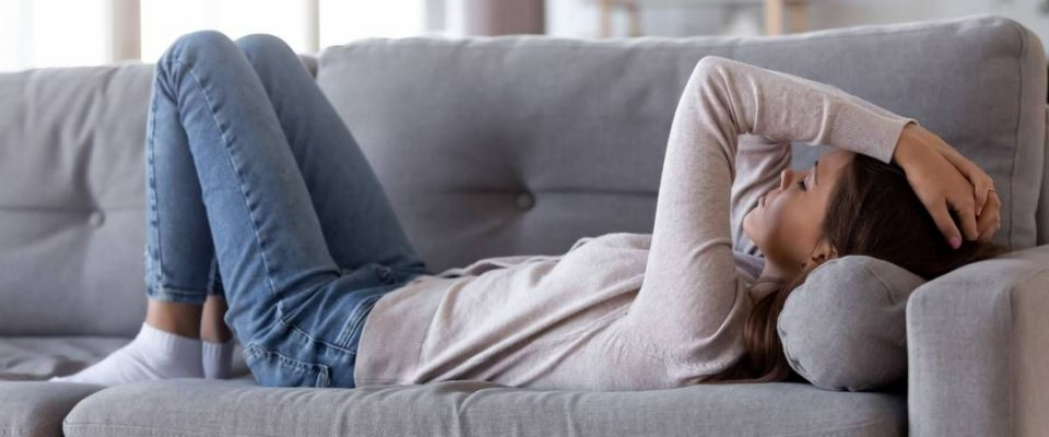 Stressed woman lying on couch