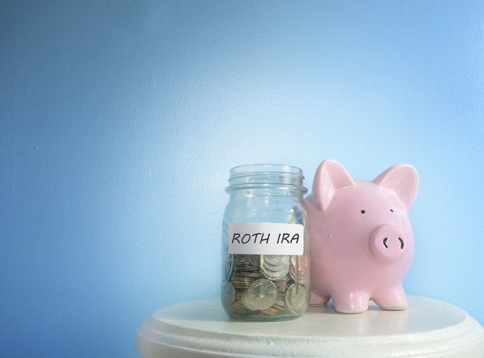Pink piggy bank sitting next to jar that says ROTH IRA on a beige table.