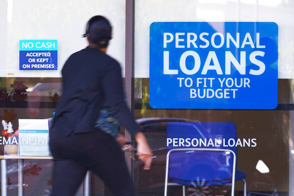 In this Oct. 1, 2020 file photo, a woman walks past a personal finance loan office in Franklin, Tenn.