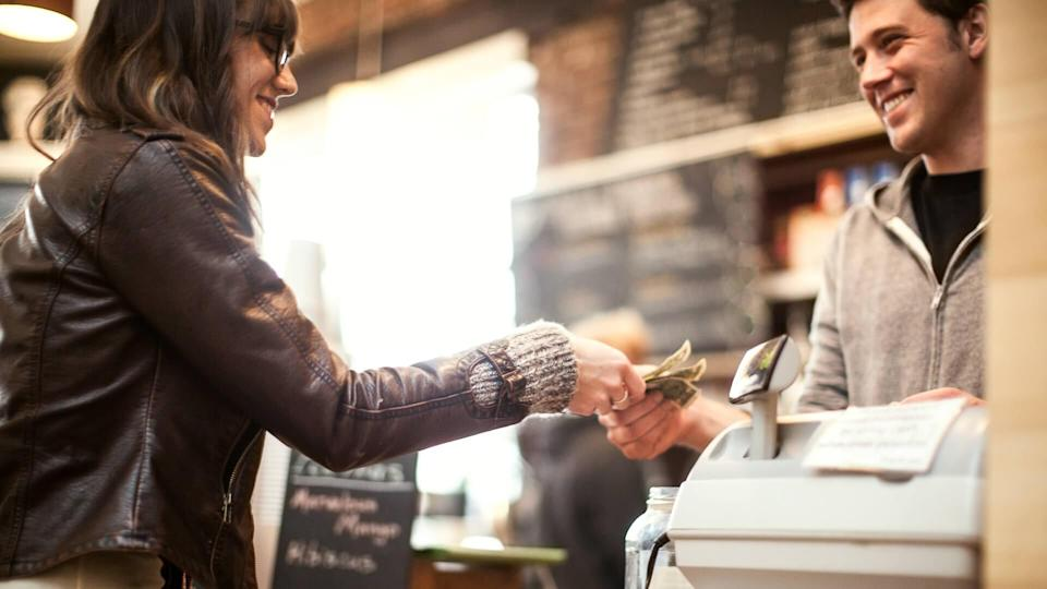 A woman is paying at a coffee shop.