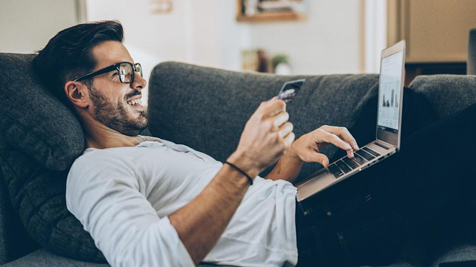 Smiling man lying on the couch and shopping online with credit card and laptop.