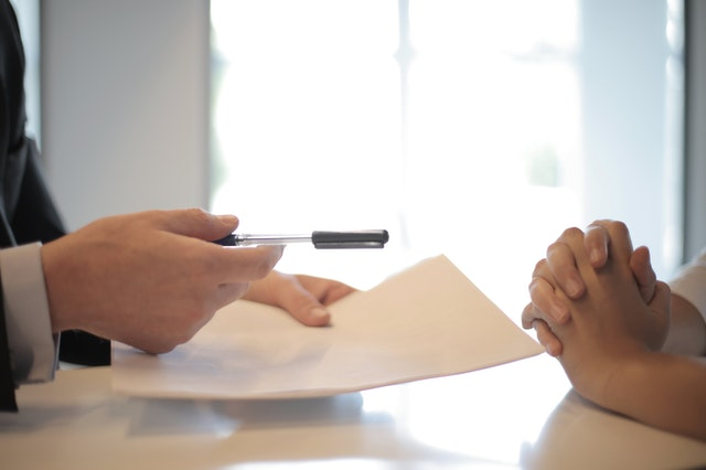 A credit repair company holding a pen and paper talking to a client about fixing their credit score.