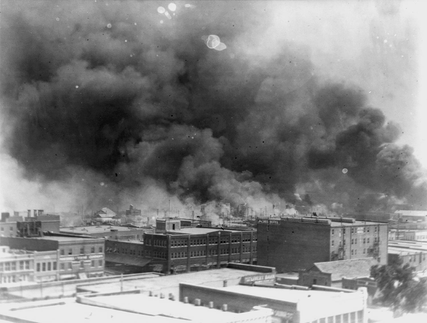 Smoke billows over Tulsa, Oklahoma on May 31, 1921, after a white mob burned down the Greenwood District, which at the time was the wealthiest Black community in the country. The mob attacked businesses on foot and fired guns out of private airplanes, destroying 35 city blocks, 1,250 homes and virtually every business in town.