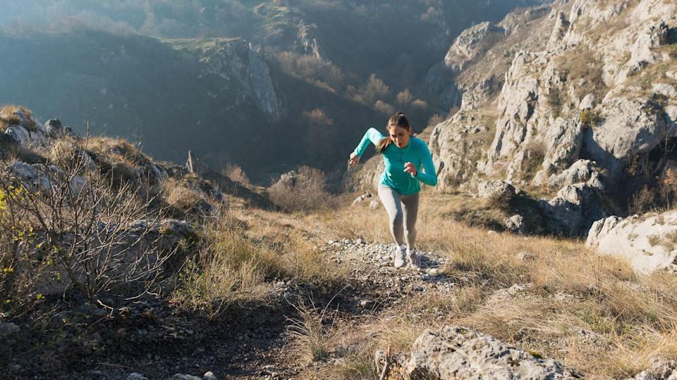 Beautiful, young female athlete running uphill.