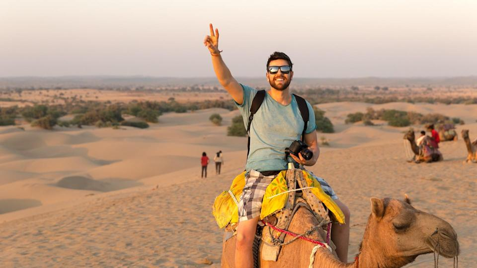 Tourist riding camel in Desert.