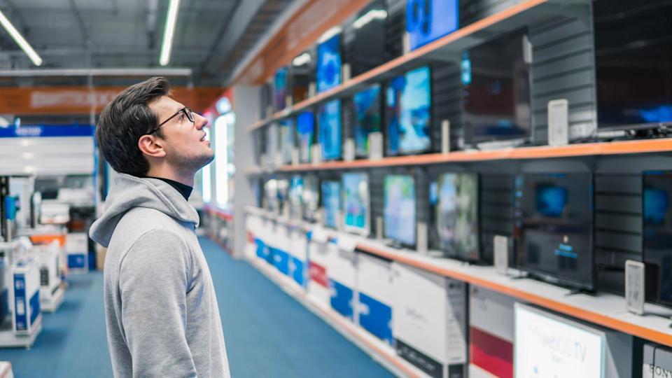 Smart modern male customer choosing large TV-sets at electronics store.