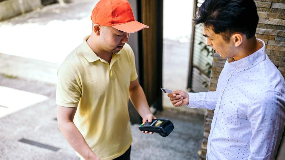 Photo of asian man paying for his food delivery at home with credit card.
