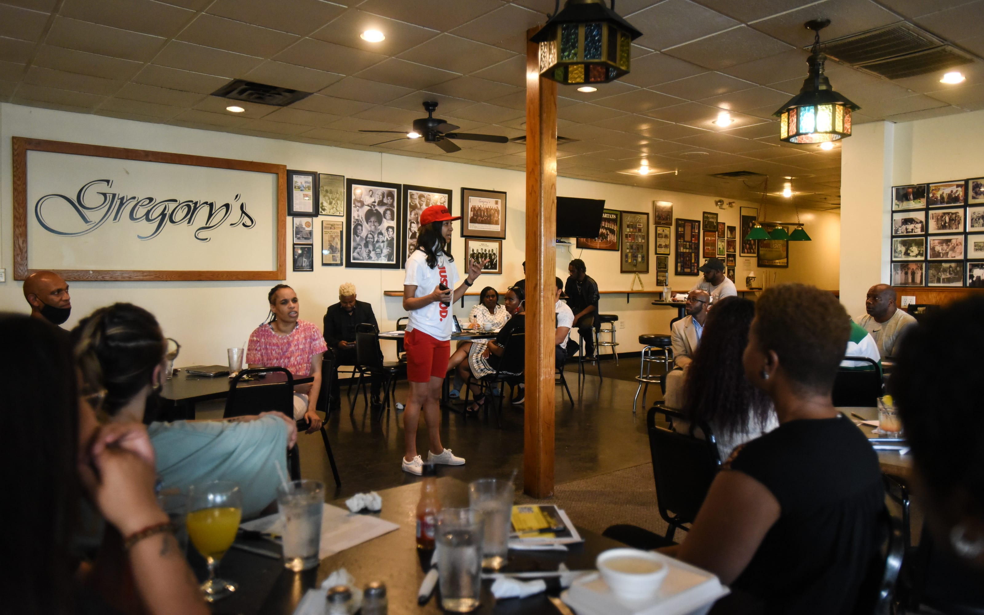 """Ashley James, a life coach and trainer known as """"Coach A'Jai,"""" speaks at Monday's Black Wall Street of Lansing networking event."""